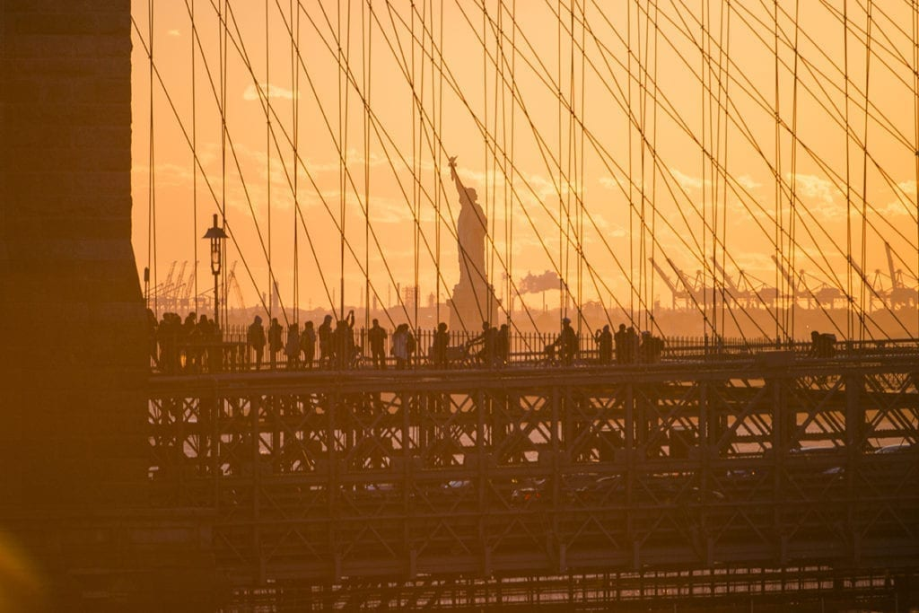 The sun sets behind the Brooklyn Bridge as with a view of the Statue of Liberty.