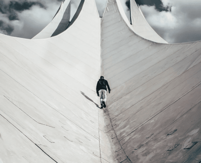angled photo of man walking up a incredibly large curved building