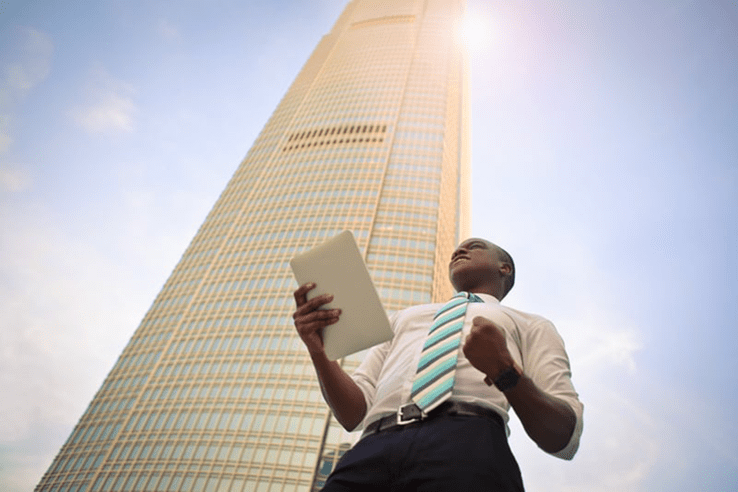 african american man in business outfit holding a document under a sky rise building.