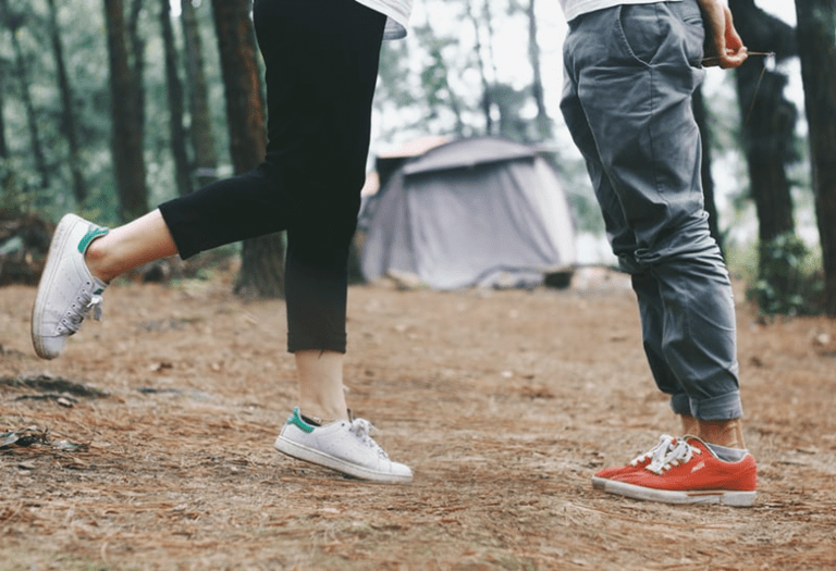 man and woman facing each other in woods camping. only shows from waste down.