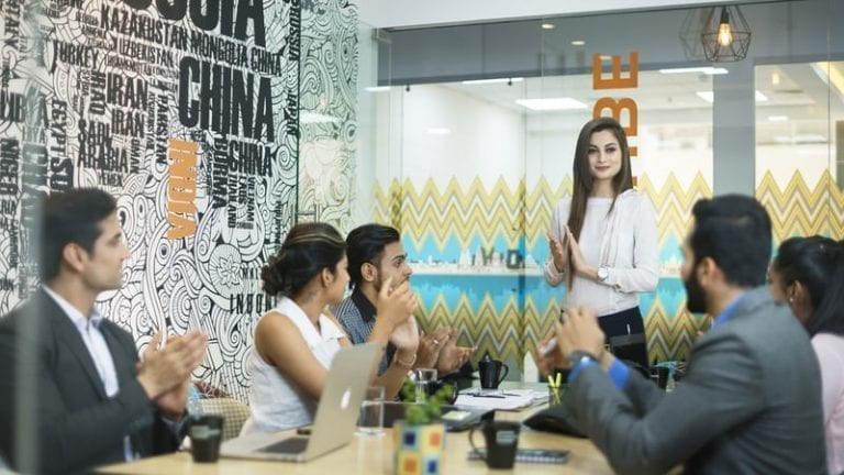 business meeting people clapping for woman